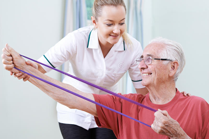 Physiotherapist Helping Senior Male To Use Resistance Band. Physiotherapist Helps Senior Male To Use Resistance Band royalty free stock photo