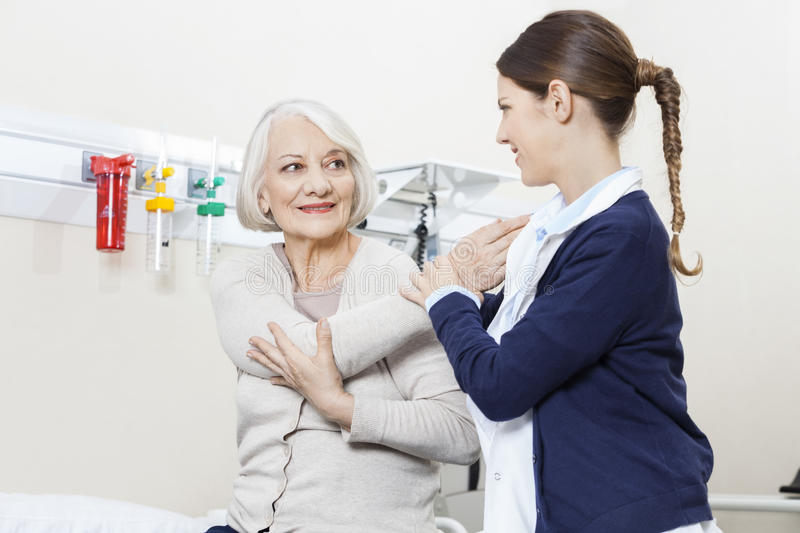 Physiotherapist Helping Smiling Senior Patient With Hand Exercis royalty free stock photography