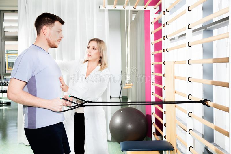 Physiotherapist helps a patient to restore movement. Doctor physiotherapist helps a patient to restore movement and function with gymnastics stretching and royalty free stock photo
