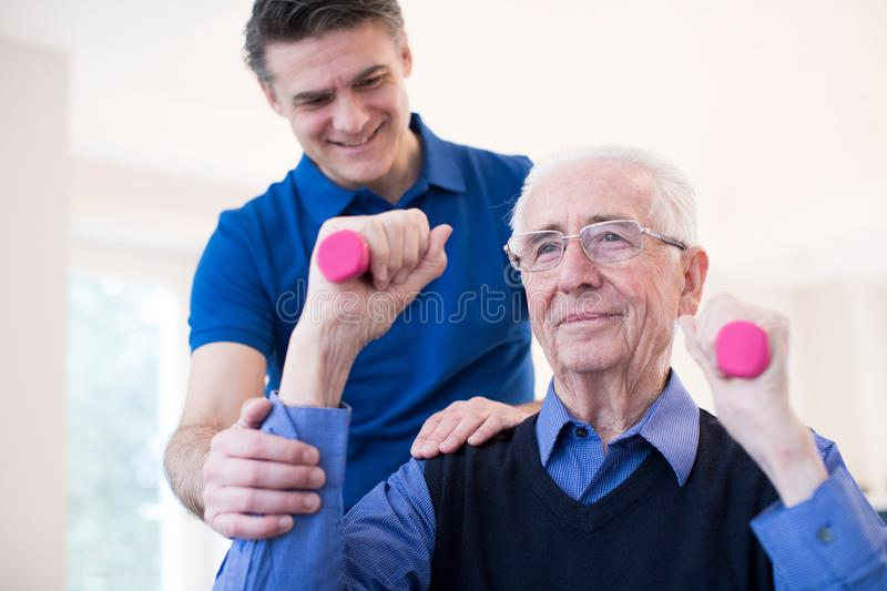 Physiotherapist Helping Senior Man To Lift Hand Weights royalty free stock photo