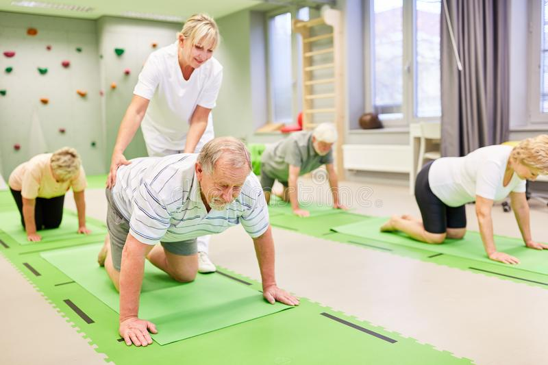 Physiotherapist looks after seniors in back exercise. Physiotherapist cares for seniors during a back exercise in physiotherapy stock image
