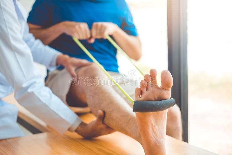 Physiotherapist mężczyzna daje oporu zespołu ćwiczenia traktowaniu O kolanie atlety Fizycznej terapii męski cierpliwy pojęcie zdjęcie stock