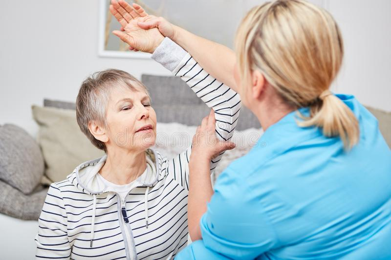 Physiotherapist makes occupational therapy exercise. With senior citizen royalty free stock photos