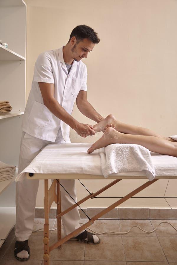Physiotherapist masażu kobiety cieki, pełny długość strzał obrazy stock