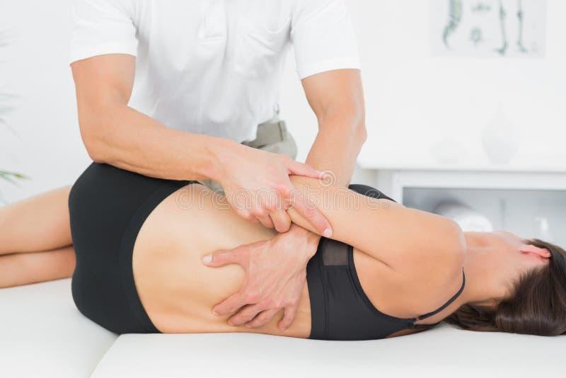 Physiotherapist masowania kobiety plecy w medycznym biurze obrazy stock