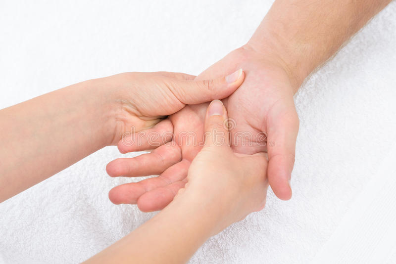 Physiotherapist massaging palm stock image
