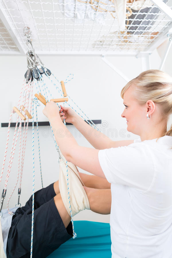 Physiotherapist with patient on sling table. Patient at the physiotherapy doing physical exercises with his therapist on sling table royalty free stock photo
