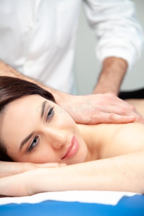 Physiotherapist practices a massage on a woman`s back. Physiotherapist practices a physiotherapeutic treatment on the back and shoulders of the patient, in the stock image