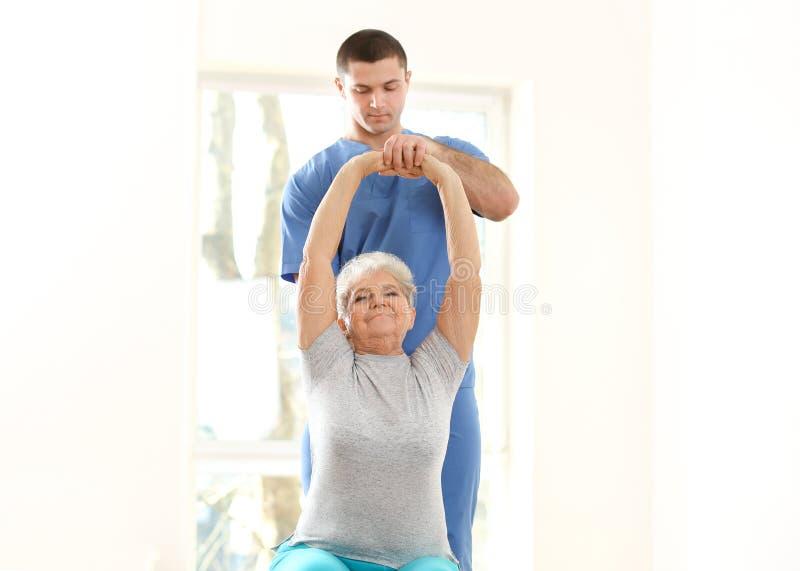 Physiotherapist pracuje z starszym pacjentem w klinice zdjęcie royalty free