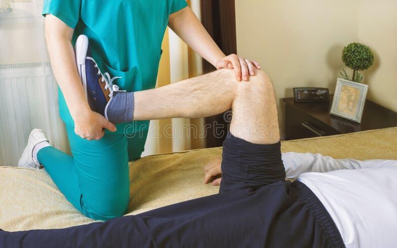 Physiotherapist robi ćwiczeniom dla nogi wyzdrowienia unieruchamiający fotografia royalty free