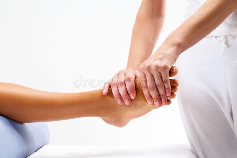 Physiotherapist robi refleksologia masażowi na żeńskiej stopie zdjęcia royalty free