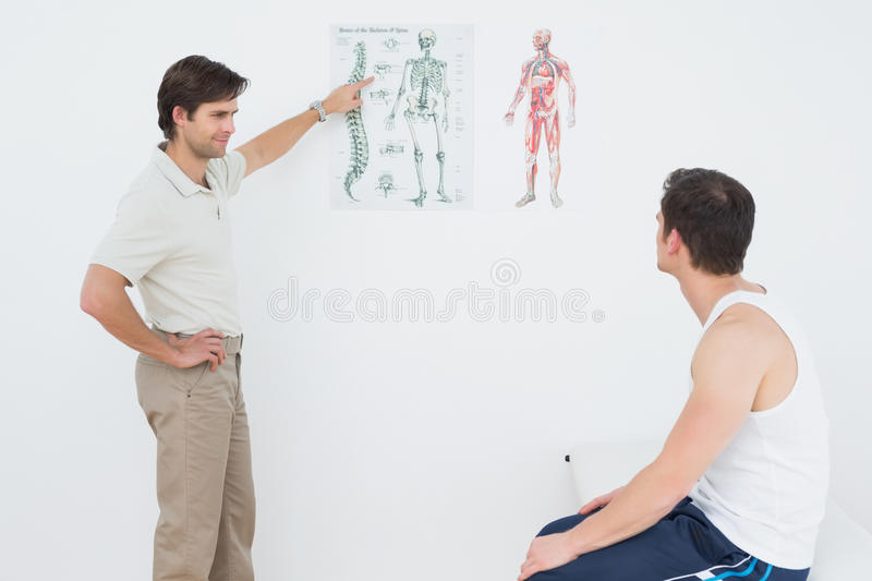 Physiotherapist showing patient something on skeleton chart. Male physiotherapist showing patient something on skeleton chart in medical office stock photos