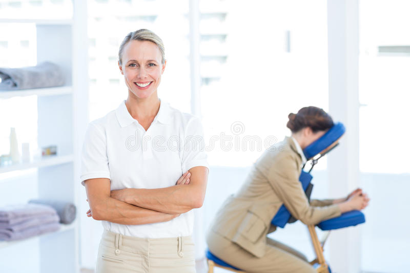 Physiotherapist smiling at camera arms crossed stock images