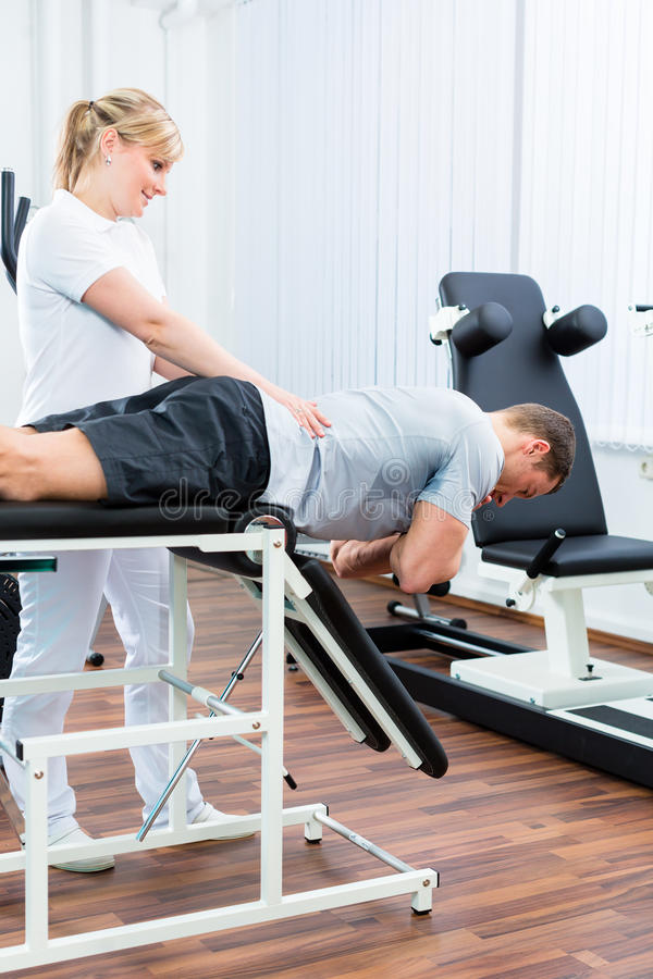 Physiotherapist or sport doctor with patient. Patient at the physiotherapy doing physical exercises with therapist with sport doctor royalty free stock photo