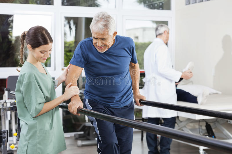 Physiotherapist Standing By Patient Walking Between Parallel Bar stock photo
