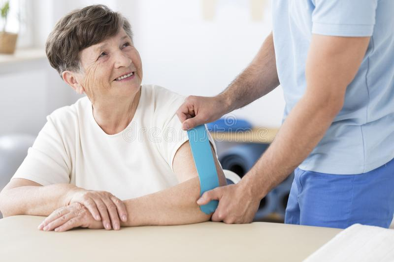 Physiotherapist sticking kinesiotape to woman royalty free stock images