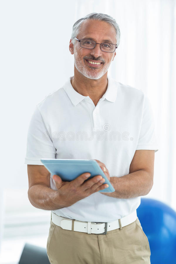 Physiotherapist using digital tablet royalty free stock image