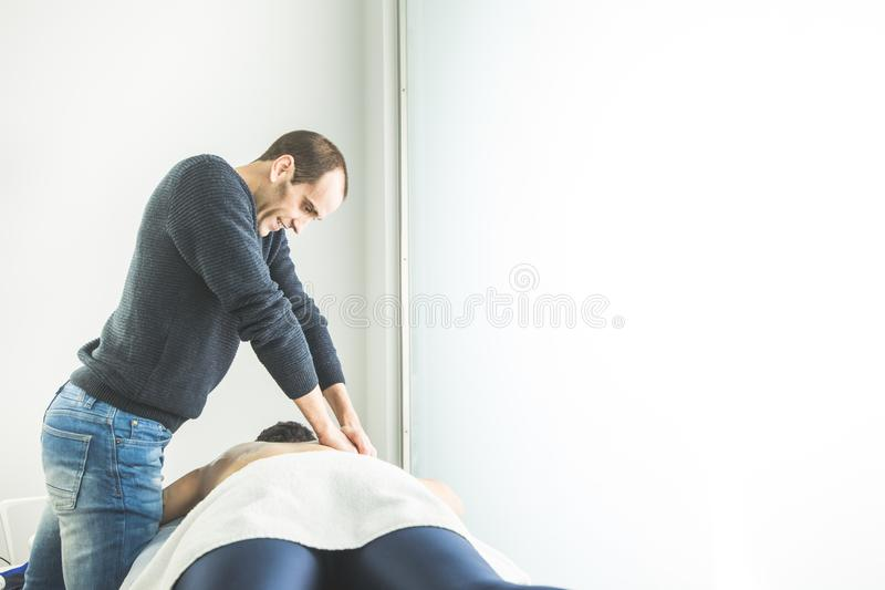 Physiotherapist working doing a massage on a patient back. Concept of physiotherapy and wellness stock images