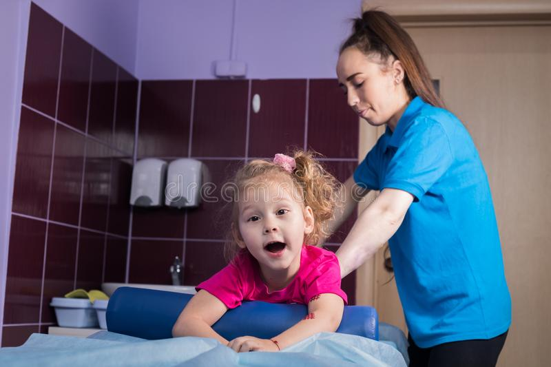 Physiotherapy with child with cerebral palsy. A little girl in clinic lays on the couch. Mid shot stock photography