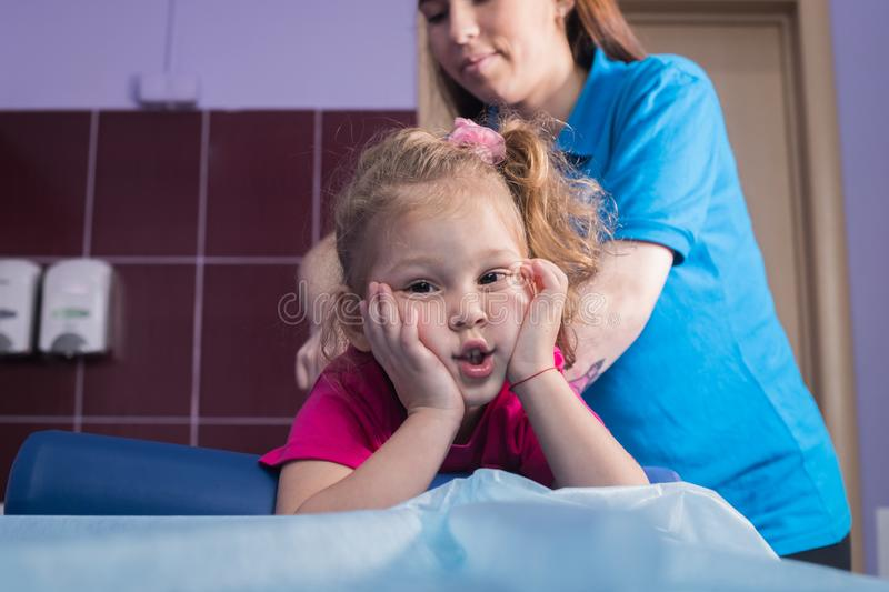 Physiotherapy with child with cerebral palsy. A little girl lays on the couch. Mid shot stock image