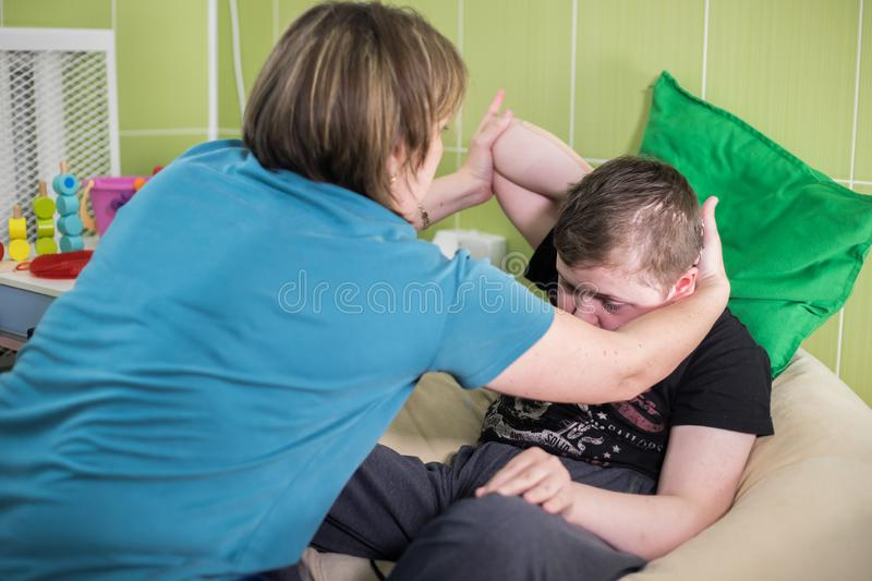 Physiotherapy with a child having a cerebral palsy. Fine motor skills developmenting. Mid shot stock image