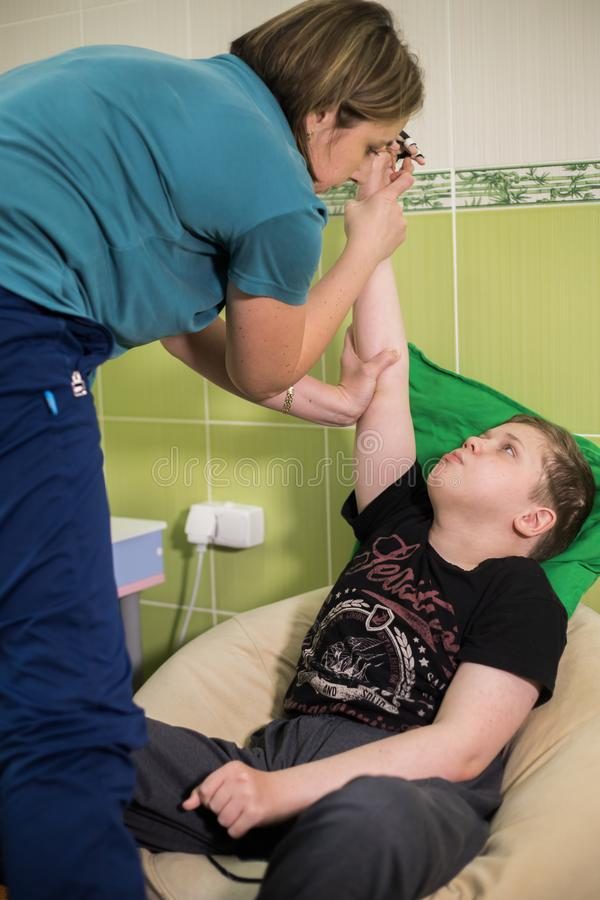 Physiotherapy with a child having a cerebral palsy. Fine motor skills developmenting. Warming up the muscles. Vertical. Shot royalty free stock photos