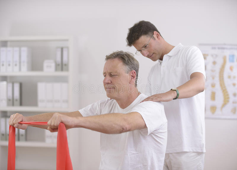 Physiotherapy: Senior man and physiotherapist royalty free stock photography