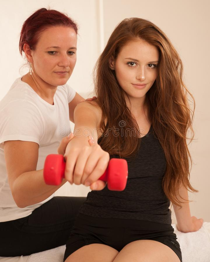 Physiotherapy - young woman making arm exercises with therapist stock image