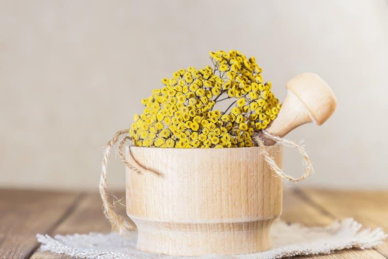 Phytotherapy, die geneeskrachtige nuttige kruiden verzamelen Droge tansy bloemen in een houten mortier met stamper op een rustiek royalty-vrije stock fotografie