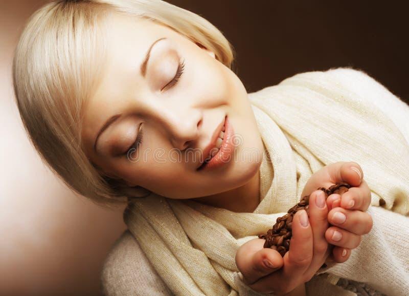 Piękna blond kobieta wącha kawowe fasole fotografia royalty free