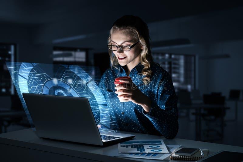 Piękna blondynka w ciemnym biurowym działaniu na laptopie i dostawać netto dostęp zdjęcia stock