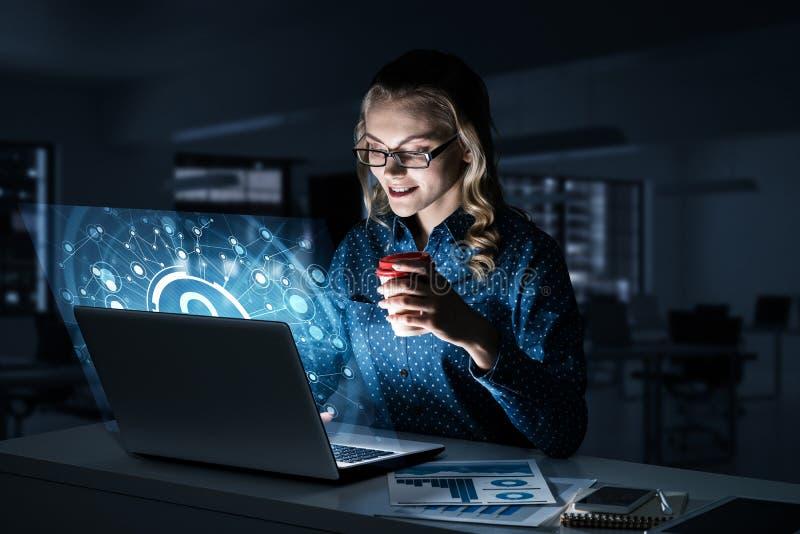Piękna blondynka w ciemnym biurowym działaniu na laptopie i dostawać netto dostęp obrazy stock