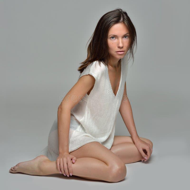Piękna bosa kobieta w białej bluzce siedzi na podłodze obrazy stock