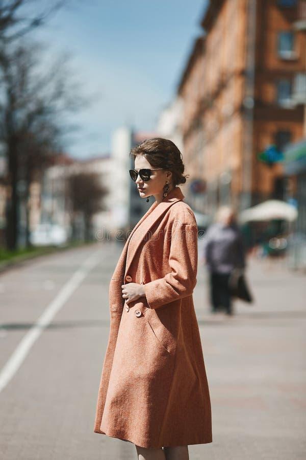 Piękna brunetka modela dziewczyna z wewnątrz modnym żakietem w modnych okularach przeciwsłonecznych pozuje przy miasto ulicą i, ż fotografia royalty free