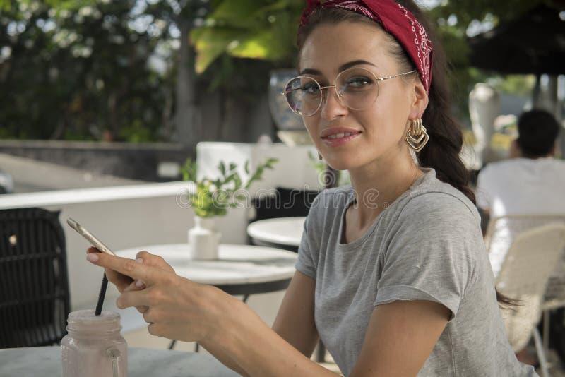 Piękna brunetka w kawiarni na ulicie pozuje z telefonem, fotografia stock