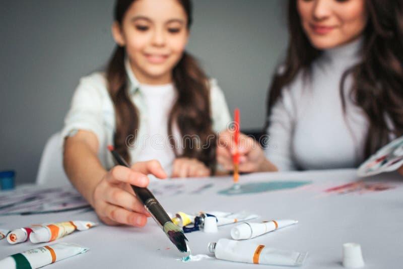 Piękna brunetki caucasian matka i córka malujemy wpólnie w pokoju Rżnięty widok i zamazujący obrazek Szczęśliwa dziewczyna stawia obraz royalty free