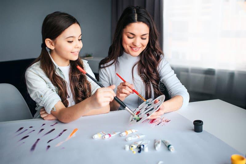 Piękna brunetki caucasian matka i córka malujemy wpólnie w pokoju Rozochoceni ludzie spojrzenie puszka i chwytów muśnięcia obraz stock