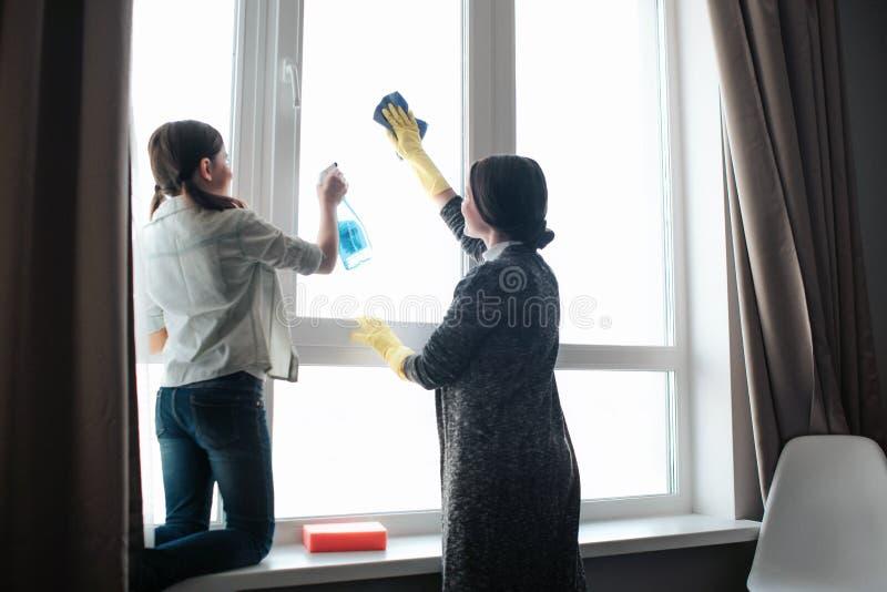 Piękna brunetki caucasian matka i córki czyści okno wpólnie w pokoju Ciężka pracująca dziewczyna używa kiść Potomstwa zdjęcia stock