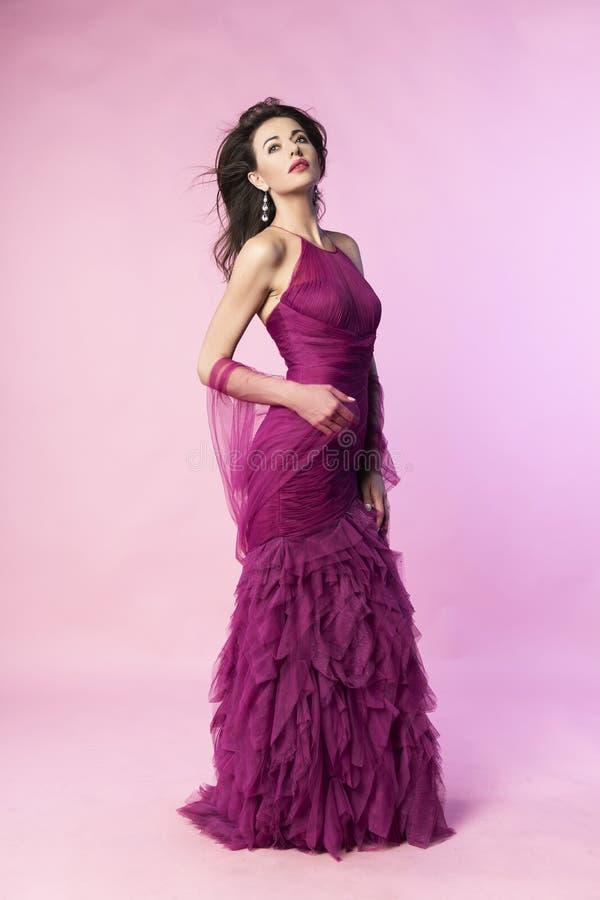 Piękna brunetki kobieta jest ubranym purpurową suknię z wiatr dmuchającym włosy, pozuje stać na różowym tle Reklamować i fotografia royalty free