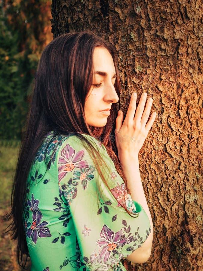 Piękna caucasian brunetki dziewczyna ubierał w sukni z kwiecistym wzorem opierającym przeciw drzewu z zamkniętymi oczami w obrazy stock