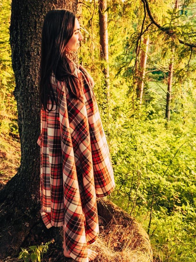 Piękna caucasian brunetki dziewczyna zawijająca w w kratkę szkockiej kracie w lesie przy zmierzch pozycją blisko drzewa dziewczyn obraz stock