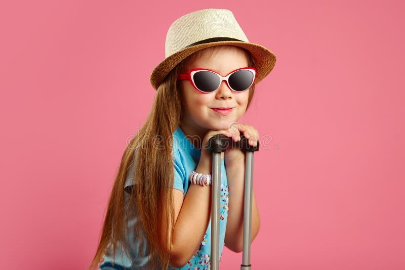 Piękna dziewczyna siedem rok w okularach przeciwsłonecznych i słomianym kapeluszu, chudy na rękojeści walizka, stojaki na odosobn fotografia stock
