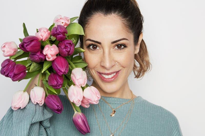 Piękna dziewczyna w błękitnej sukni z kwiatów tulipanami w rękach na lekkim tle fotografia stock