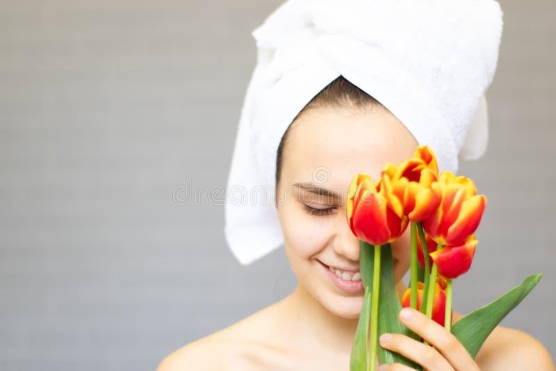 Piękna dziewczyna z kwiatów tulipanami w rękach na lekkim tle obrazy stock