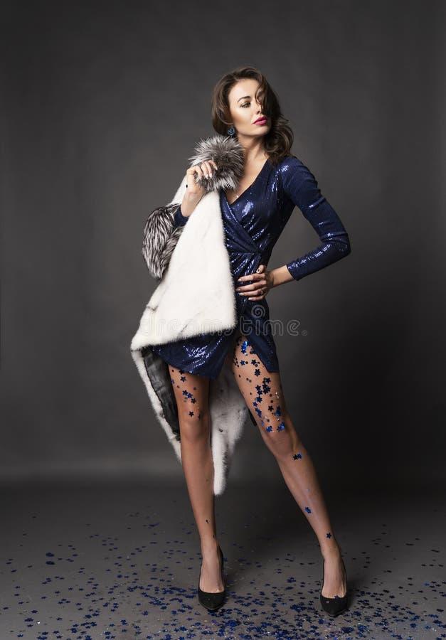 Piękna elegancka brunetki kobieta jest ubranym genialną błękit suknię i futerkowego żakiet z jej nogami zakrywać z błyskotliwość  obrazy stock