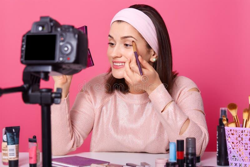 Piękna kobieta nagrywa wideo Yong blogger przedstawienia dlaczego stosować eyeshadow Dam advetises kosmetyki na ona korytkowa Kob obraz royalty free