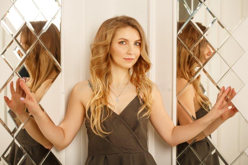 Piękna kobieta pozuje blisko lustra fotografia stock