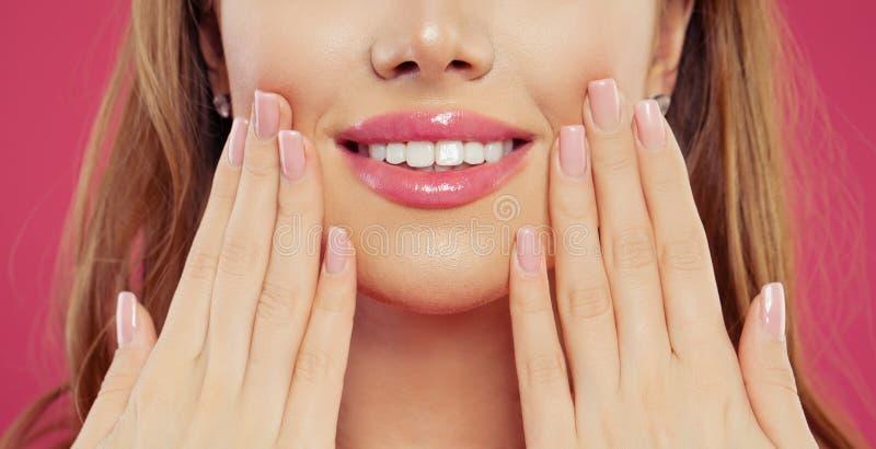 Piękna kobieta uśmiecha się jej rękę z manicure gwoździami z naturalnym różowym gwoździa połyskiem i pokazuje Makeup wargi fotografia royalty free