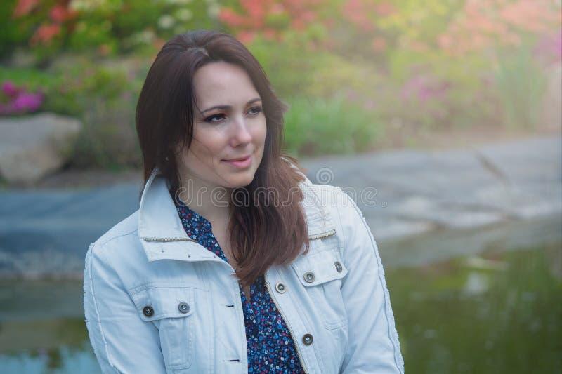 Piękna kobieta w białej kurtce w ogródzie zdjęcia stock