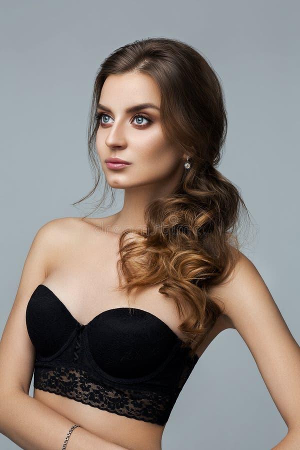 Piękna kobieta z makijażem i fryzura nad popielatym tłem zdjęcia stock